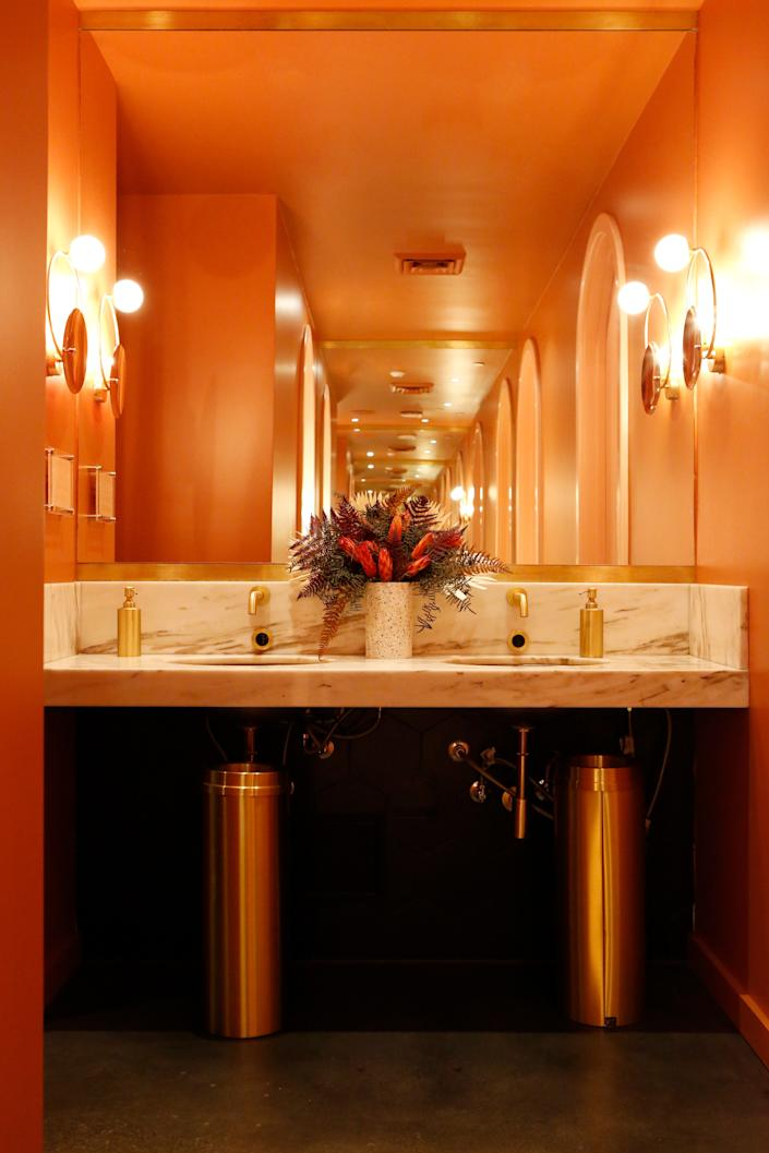 """<div class=""""caption""""> The warm glow in the bathroom sets a very different, though still glamorous, tone within the restaurant. </div> <cite class=""""credit"""">Lu Tapp</cite>"""