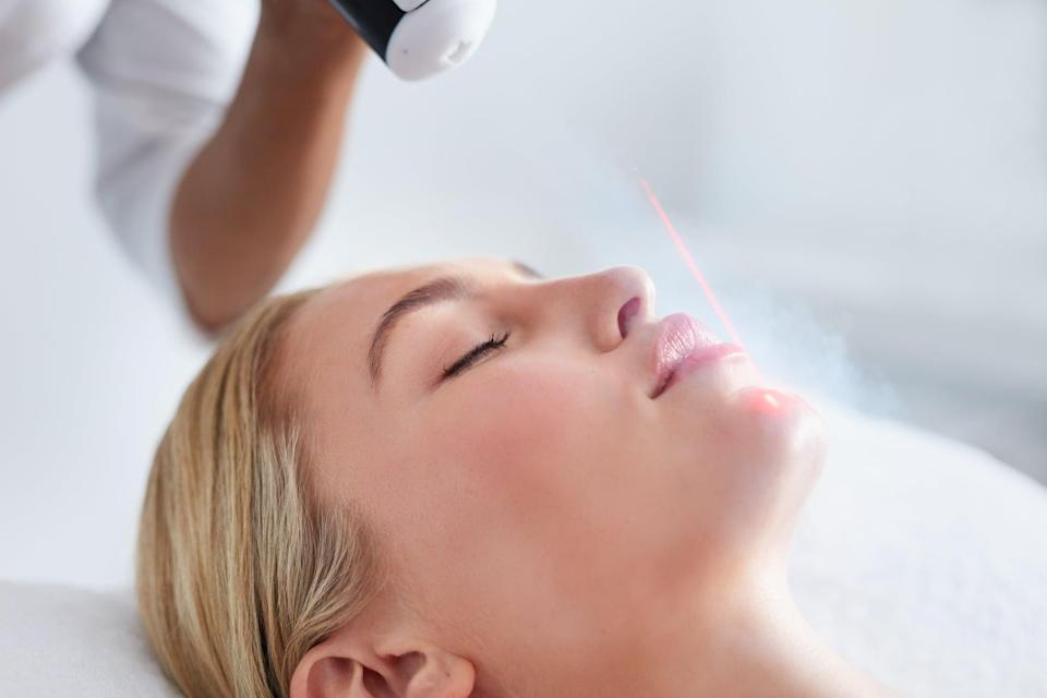 Close up of face of young woman receiving local cryotherapy. Beauty treatment using vaporized nitrogen.