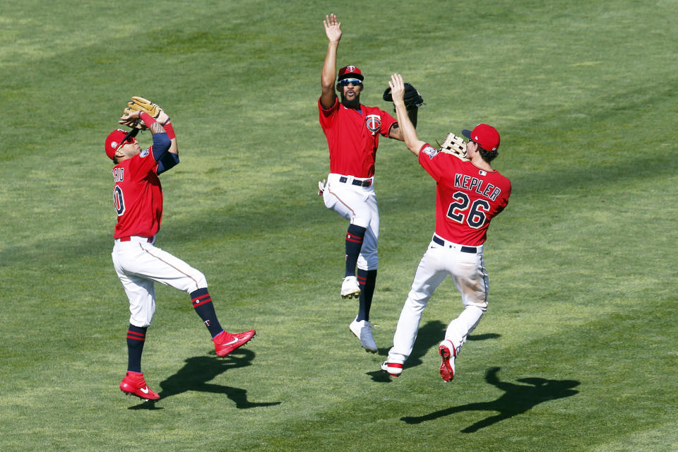 Minnesota Twins outfielders, from left, Eddie Rosario, Byron Buxton, and Max Kepler celebrate the Twins win over the Pittsburgh Pirates with their basketball shooting prowess Tuesday, Aug. 4, 2020, in Minneapolis. (AP Photo/Jim Mone)