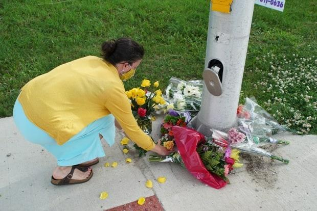 A woman lays flowers at a growing memorial at the site of a crash that killed four members of a Muslim family. Police believe they were targeted on account of their faith.  (Colin Butler/CBC News - image credit)
