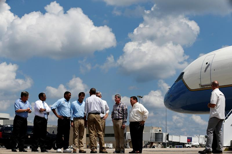 U.S. President Barack Obama (back to camera, 5th L) speaks with local and state officials as he arrives aboard Air Force One at Baton Rouge Metropolitan Airport in Baton Rouge, Louisiana, U.S., August 23, 2016. REUTERS/Jonathan Ernst