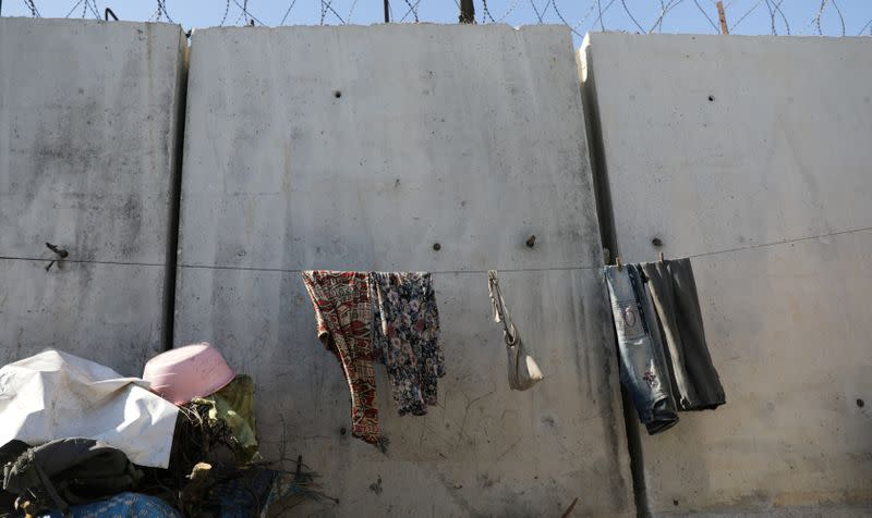 FILE PHOTO: Clothes are hanged on a rope to dry near the wall in Atmah IDP camp, located near the border with Turkey