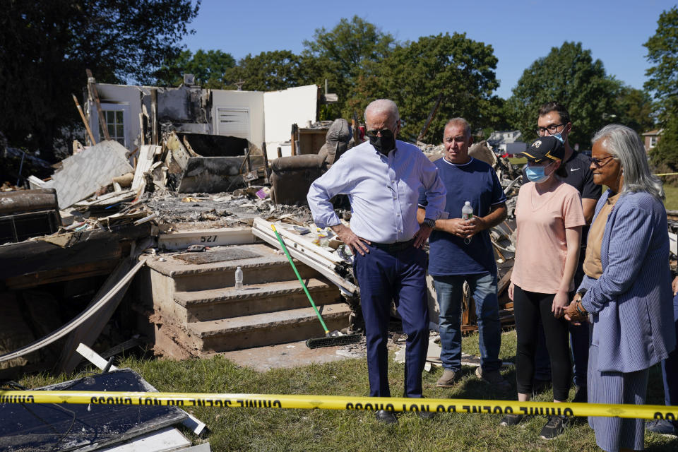 """FILE - In this Sept. 7, 2021, file photo President Joe Biden tours a neighborhood impacted by Hurricane Ida in Manville, N.J. Rep. Bonnie Watson Coleman, D-N.J., looks on at right. Surveying damage from California wildfires to hurricane-induced flooding in Louisiana and New York Biden said America must get serious about the """"code red"""" danger posed by global warming. (AP Photo/Evan Vucci, File)"""