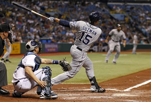 San Diego Padres' Jesus Guzman follows through on a pinch-hit grand slam home run in front of Tampa Bay Rays catcher Jose Lobaton during the seventh inning of an interleague baseball game Saturday, May 11, 2013, in St. Petersburg, Fla. (AP Photo/Mike Carlson)