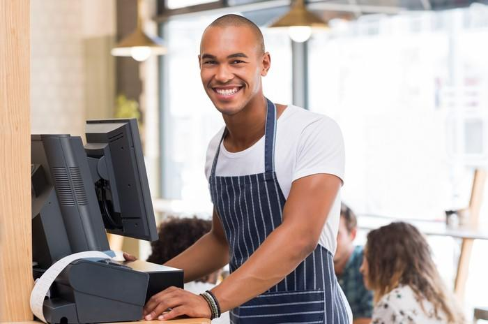 A young man working as a server in a restaurant.
