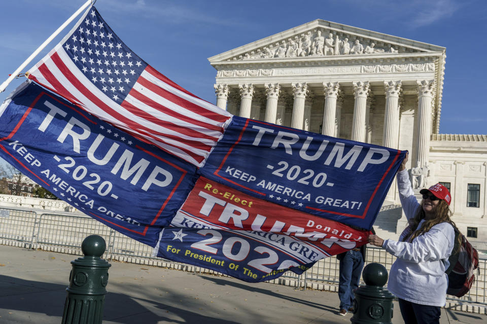 FILE - In this Dec. 11, 2020 file photo, Kathy Kratt of Orlando, Fla., displays her Trump flags as she and other protesters demonstrate their support for President Donald Trump at the Supreme Court in Washington. The Supreme Court has formally rejected a handful of cases related to the 2020 election, including disputes from Pennsylvania that had divided the justices just before the election. The cases the justices rejected involved election challenges filed by former President Donald Trump and his allies in five states President Joe Biden won: Arizona, Georgia, Michigan, Pennsylvania and Wisconsin.(AP Photo/J. Scott Applewhite)