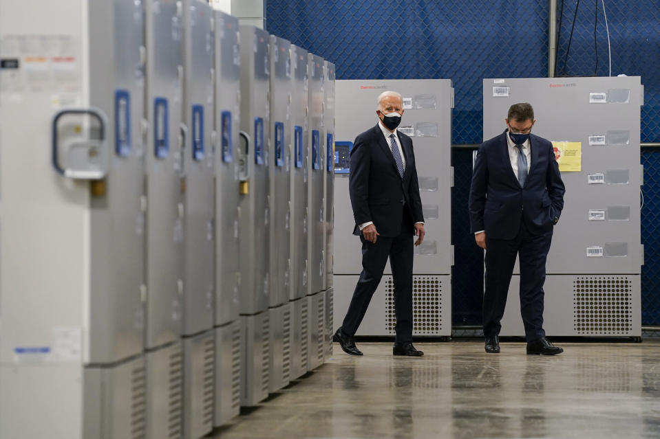 FILE - In this Feb. 19, 2021, file photo President Joe Biden walks by freezers used to hold the Pfizer COVID-19 vaccine as he tours a Pfizer manufacturing site with Albert Bourla, Pfizer CEO, in Portage, Mich. (AP Photo/Evan Vucci, File)