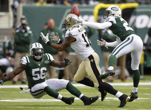 New Orleans Saints Robert Meachem (C) makes a catch on a ball tipped by New York Jets Dee Miller (R) in front of Jets Demario Davis (L) in the first quarter during their NFL football game in East Rutherford, New Jersey, November 3, 2013. REUTERS/Gary Hershorn (UNITED STATES - Tags: SPORT FOOTBALL)