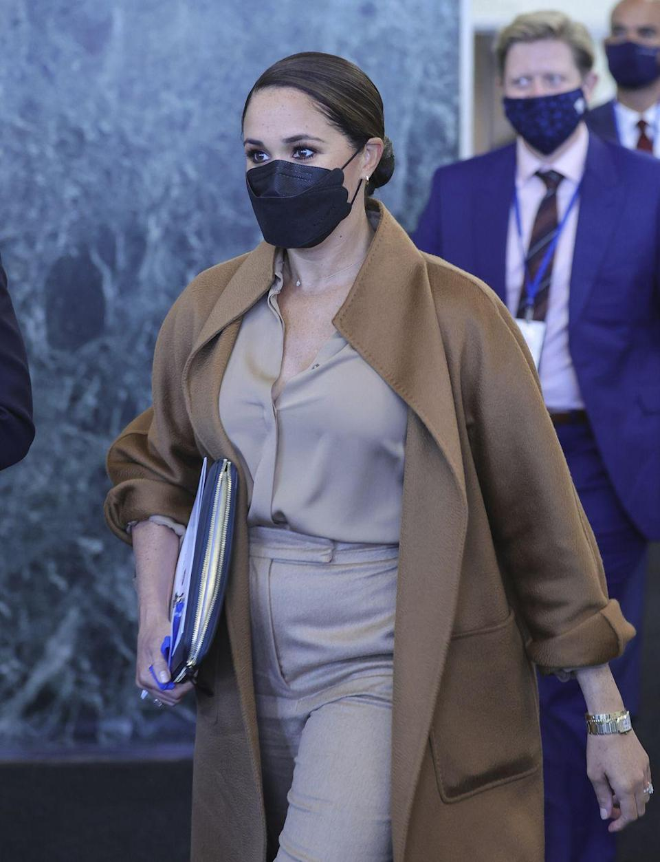 <p>Meghan wore a MaxMara coat for the occasion, paired with a neutral shirt and matching trousers. </p>