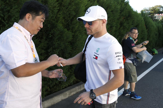 Mercedes driver Valtteri Bottas of Finland returns a pen after signing his autograph to a fan upon arrival at the paddock ahead of the Japanese Formula One Grand Prix at Suzuka Circuit in Suzuka, central Japan, Sunday, Oct. 13, 2019. (AP Photo/Toru Takahashi)