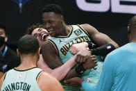 Charlotte Hornets guard Terry Rozier celebrates after scoring the game winning basket with LaMelo Ball, left, against the Golden State Warriors during an NBA basketball game on Saturday, Feb. 20, 2021, in Charlotte, N.C. (AP Photo/Chris Carlson)
