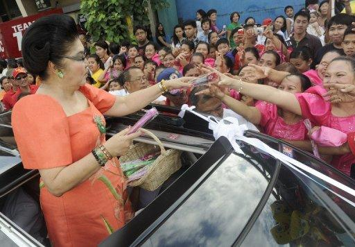 Former Philippine first lady Imelda Marcos hands out candies in Manila