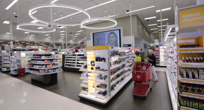 In this May 30, 2018, photo, shoppers look through the updated cosmetic department at a Target store in San Antonio. Success of specialty chains like Sephora and Ulta has pushed discounters like Walmart and Target as well as drugstores like CVS to revamp their cosmetics areas with more open spaces, brighter lighting and more attractive fixtures. (AP Photo/Eric Gay)