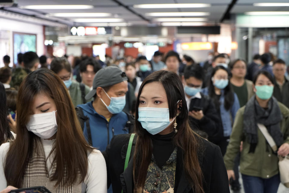 Passengers wear masks to prevent an outbreak of a new coronavirus in a subway station, in Hong Kong, Wednesday, Jan. 22, 2020. The first case of coronavirus in Macao was confirmed on Wednesday, according to state broadcaster CCTV. The infected person, a 52-year-old woman, was a traveller from Wuhan. (AP Photo/Kin Cheung)