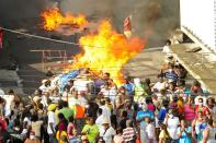 A fire burns near people protesting against amendments to the Public Health Act in Kingstown