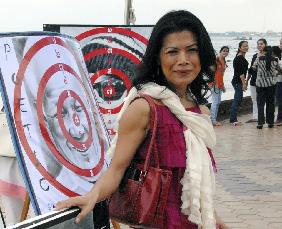 FILE - In this Nov. 18, 2012, file photo, activist Theary Seng poses with dart board posters during a protest in Phnom Penh, Cambodia. Activist and lawyer Theary Seng, is one of dozens of people have been targeted by Cambodian government in its most severe legal offensive against its political opponents in three years. (AP Photo/Luke Hunt, File)