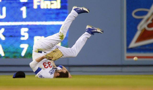 Los Angeles Dodgers left fielder Scott Van Slyke can't get to a ball hit for an RBI double by Colorado Rockies' Nolan Arenado during the fourth inning of their baseball game, Saturday, Sept. 28, 2013, in Los Angeles. (AP Photo/Mark J. Terrill)