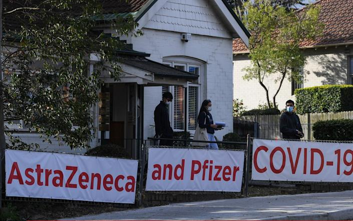 People pass a doctor's surgery offering the AstraZeneca and Pfizer vaccines in the suburb of Lane Cove, Sydney - Getty