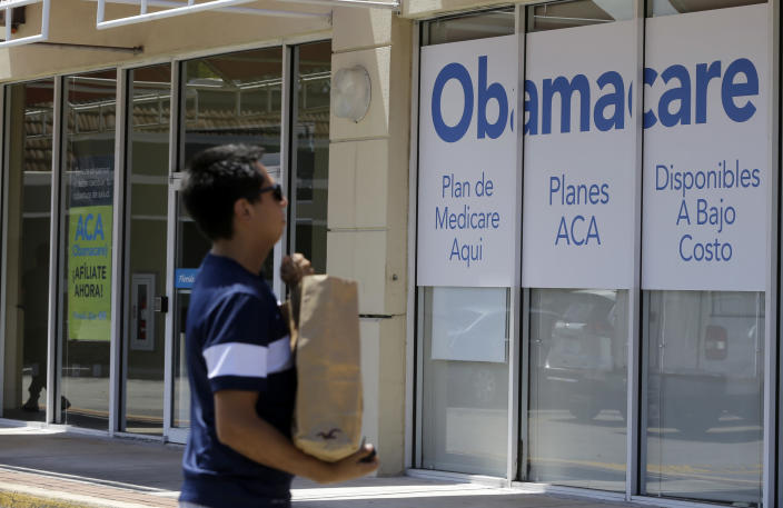 This photo taken Thursday, July 27, 2017, shows a man walks by an healthcare insurance office in Hialeah, Fla. (AP Photo/Alan Diaz)