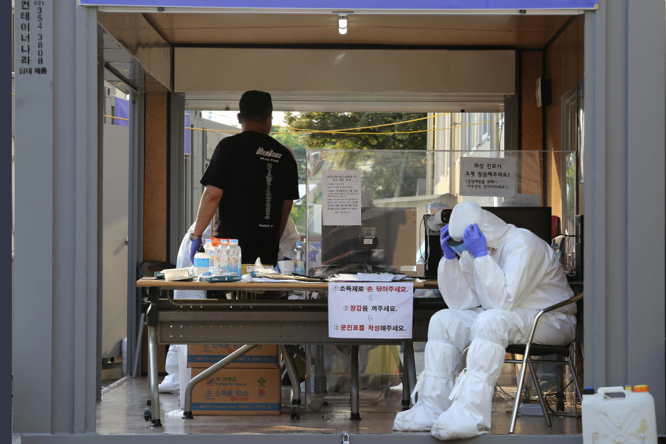 A health official wearing protective gear takes a rest during the COVID-19 testing at a public health center in Goyang, South Korea, Thursday, May 28, 2020. South Korea on Thursday reported its biggest jump in coronavirus cases in more than 50 days, a setback that could erase some of the hard-won gains that have made it a model for the rest of the world. (AP Photo/Ahn Young-joon)