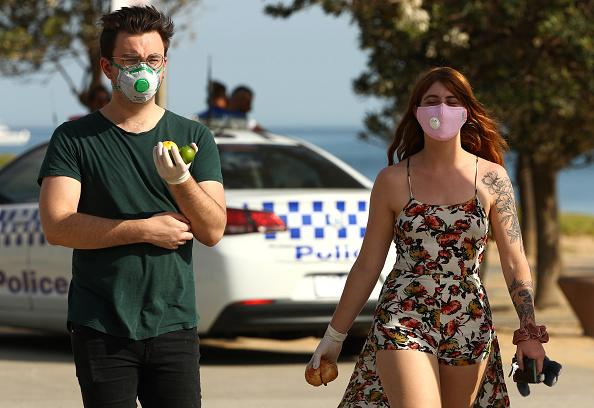 People are seen at St Kilda Beach in Melbourne wearing face masks.