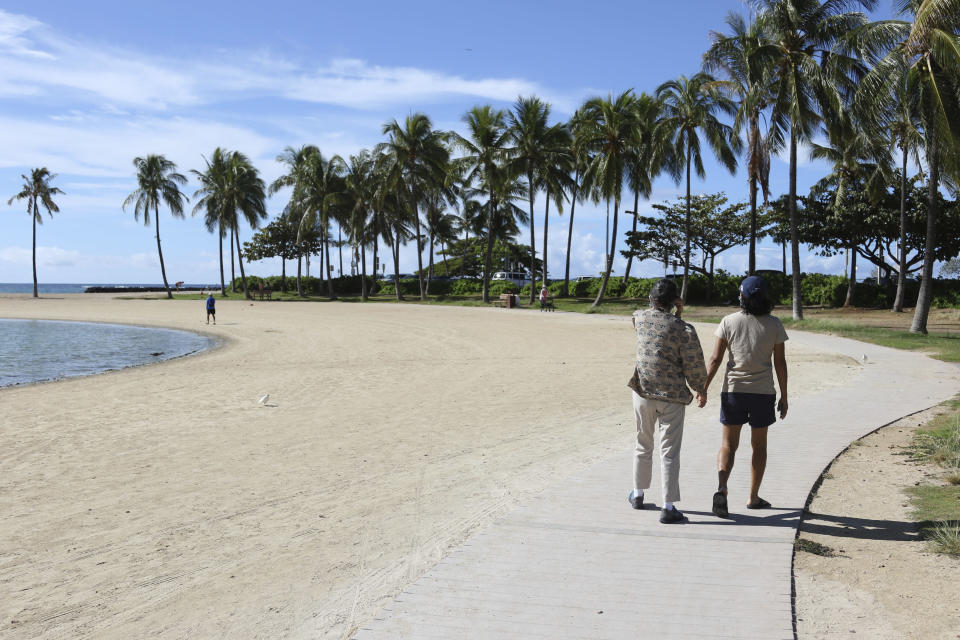Two women walk on a nearly empty Waikiki Beach in Honolulu, Friday, Oct. 2, 2020. After a summer marked by a surge of coronavirus cases in Hawaii, officials plan to reboot the tourism based economy later this month despite concerns about the state's pre-travel testing program. (AP Photo/Caleb Jones)