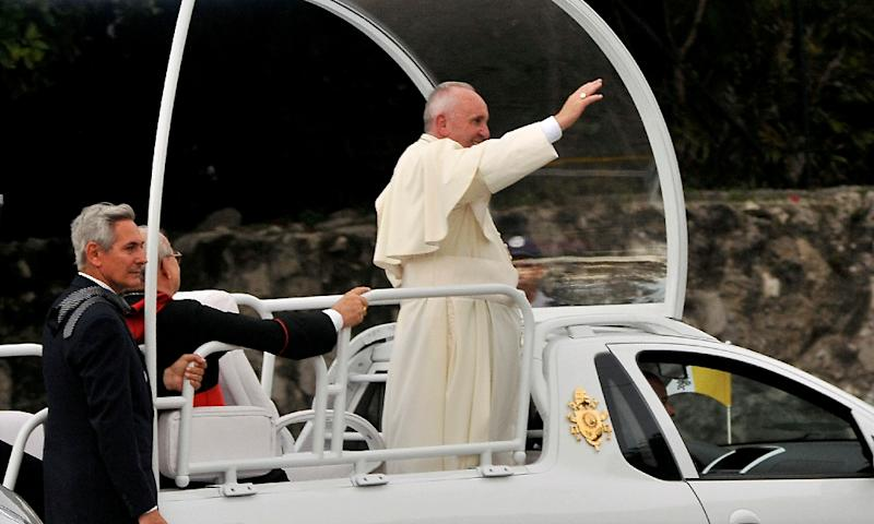 Pope Francis waves from the Popemobile as he is driven from Jose Marti international airport to Havana's downtown during his visit to Cuba on September 19, 2015 (AFP Photo/Pedro Torres)
