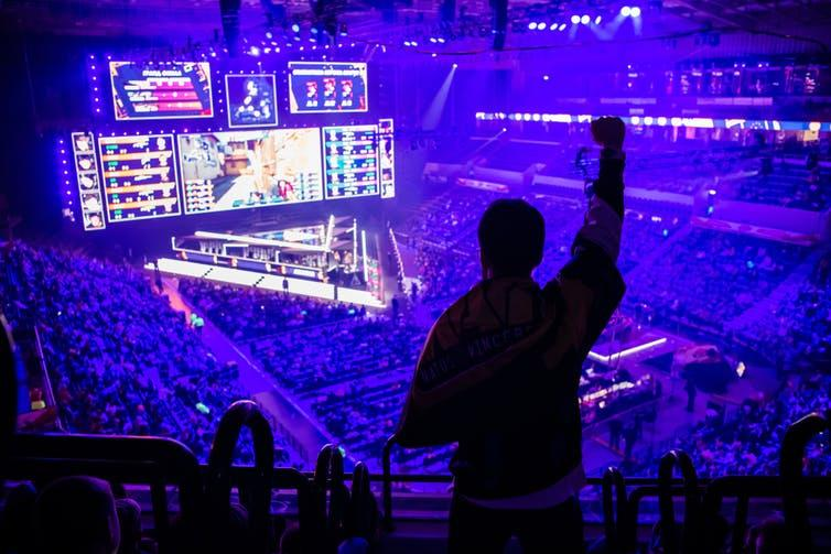 Fan standing up in mass audience for esports event in Moscow