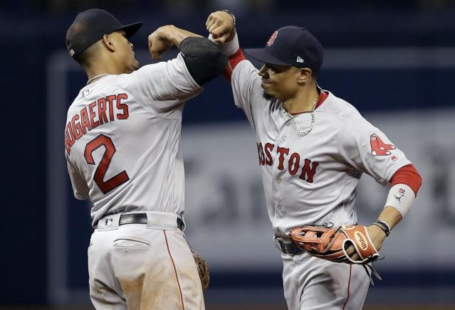 Xander Bogaerts (left) and Mookie Betts celebrate a Red Sox win in Sept. 2017. (AP)