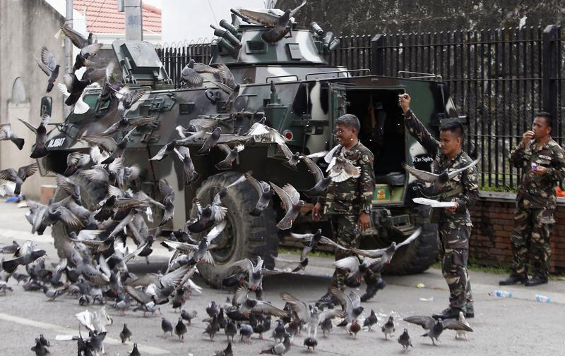 Government soldiers of Task Force Zamboanga feed pigeons with bread crumbs near a military command post during a lull in fighting with Muslim rebels of Moro National Liberation Front (MNLF), in Zamboanga city in southern Philippines September 16, 2013. REUTERS/Erik De Castro