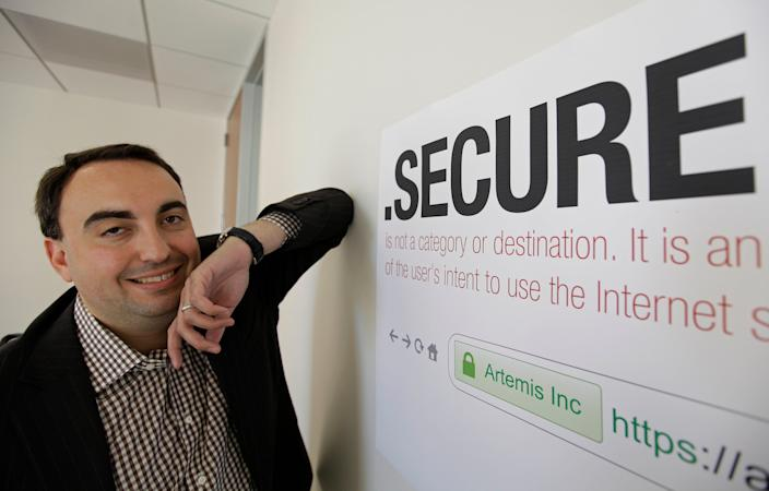 In this photo taken Friday, June 8, 2012 Alex Stamos, then-CTO of Artemis Internet, an NCC Group Company, poses by a domain name poster at their offices in San Francisco. (AP Photo/Eric Risberg, File)
