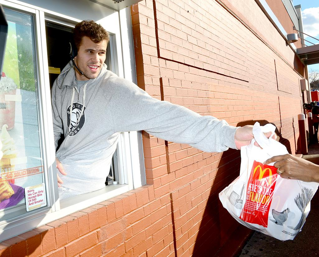 """NEW YORK, NY - JANUARY 31:  Brooklyn Nets player Kris Humphries participates in the """"Random Acts of Kindness"""" program by serving McDonald's customers in the Prospect Lefferts Gardens neighborhood of Brooklyn on January 31, 2013 in New York City.  (Photo by James Devaney/WireImage)"""