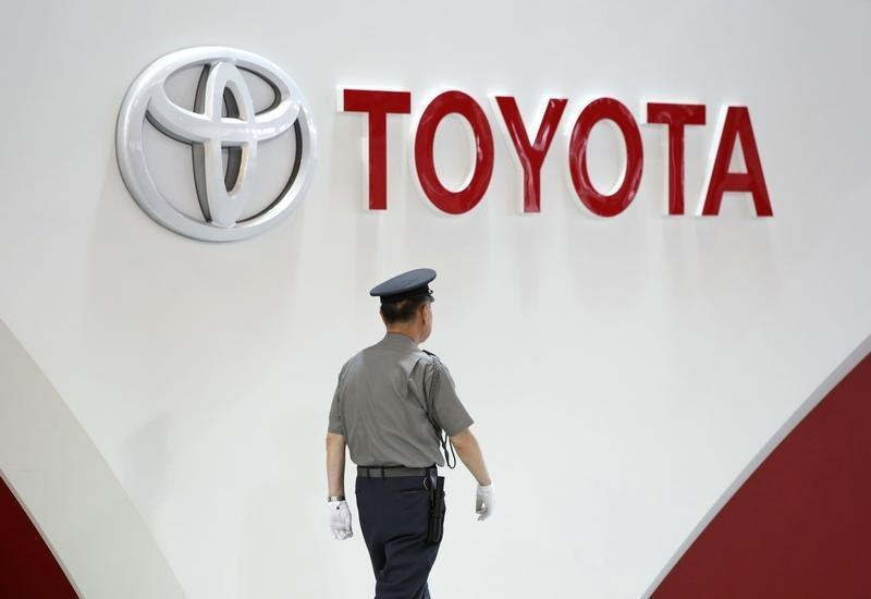 A security guard walks under the logo of Toyota Motor Corp in Tokyo