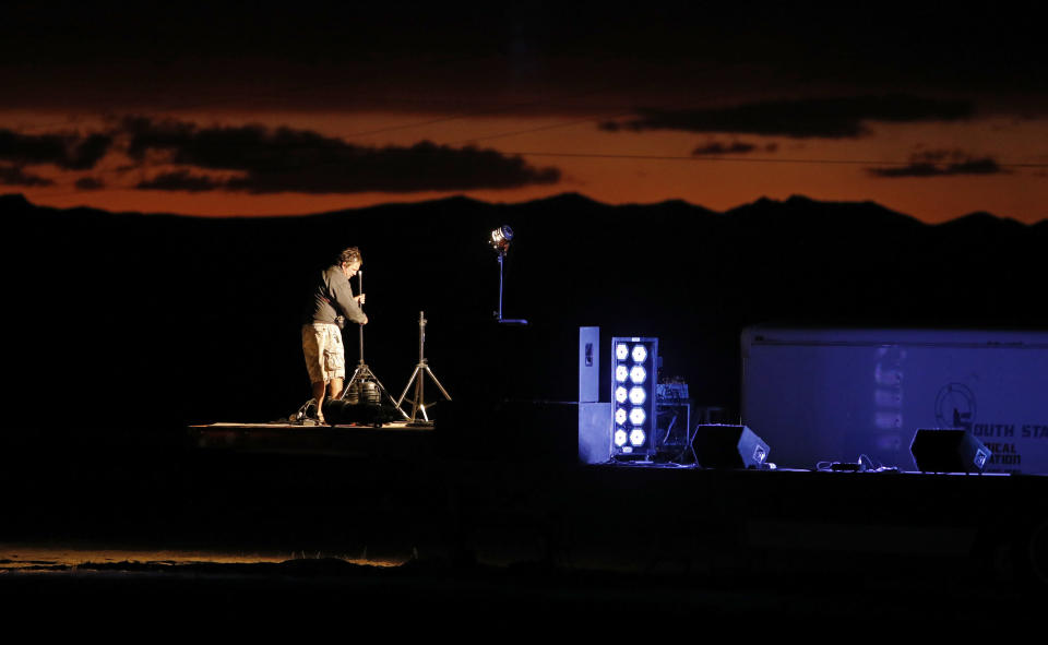 """A man sets up a stage in preparation for an event inspired by the """"Storm Area 51"""" internet hoax near the Little A'Le'Inn motel and cafe, Thursday, Sept. 19, 2019, in Rachel, Nev. Hundreds have arrived in the desert after a Facebook post inviting people to """"see them aliens"""" got widespread attention and gave rise to festivals this week. (AP Photo/John Locher)"""