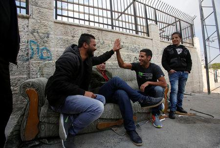 Nuseir Yassin holds the hand of a Palestinian man as he is filmed in Aida refugee camp in the West Bank city of Bethlehem March 2, 2017. REUTERS/Mussa Qawasma