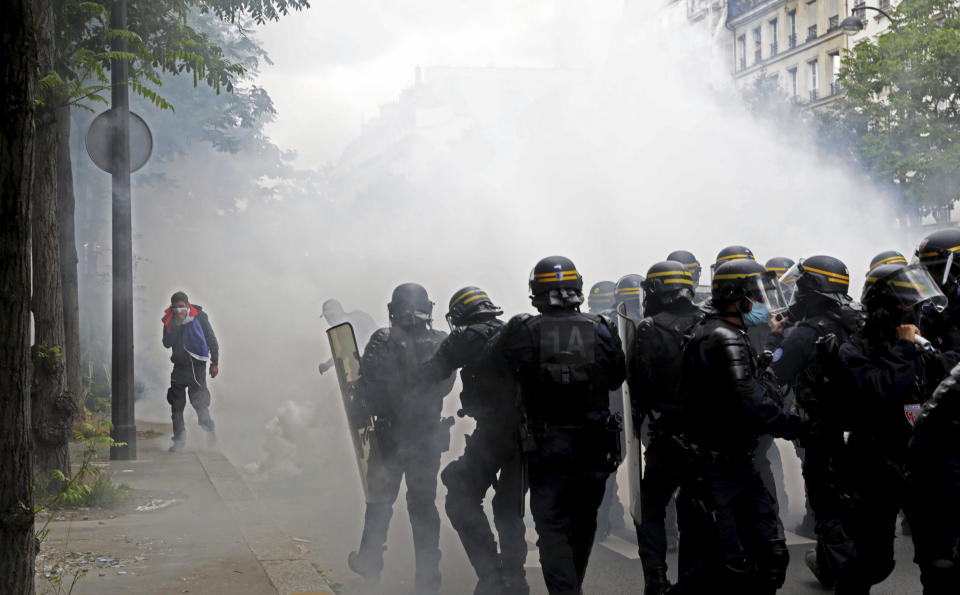 A protestor covers their face against gas canisters as police move their line during a demonstration in Paris, France, Saturday, July 31, 2021. Demonstrators gathered in several cities in France on Saturday to protest against the COVID-19 pass, which grants vaccinated individuals greater ease of access to venues. (AP Photo/Adrienne Surprenant)