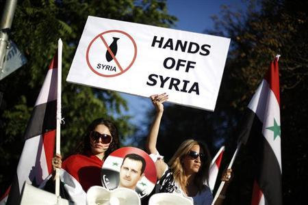 Protesters hold banners during a demonstration against potential U.S. strikes on Syria, in front of the U.S. embassy in Sofia September 4, 2013. REUTERS/Stoyan Nenov