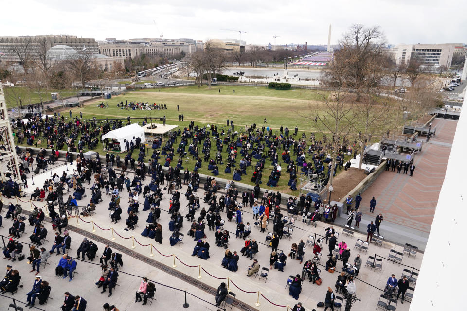 Attendees sit on the West Front of the U.S. Capitol at the 59th Presidential Inauguration in Washington, Wednesday, Jan. 20, 2021. (Kevin Dietsch/Pool Photo via AP)