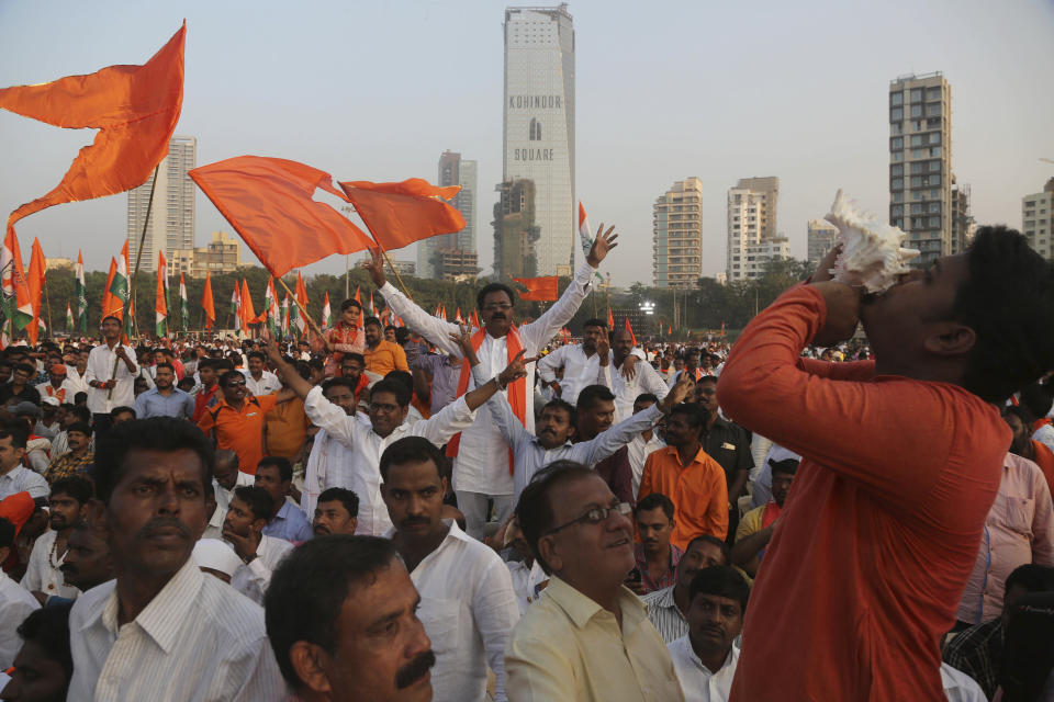 Supporters of Shiv Sena, Nationalist Congress Party (NCP) and the Congress party shout slogans as they wait for the swearing-in ceremony of Shiv Sena party leader Uddhav Thackeray as chief minister of Maharashtra state in Mumbai, India, Thursday, Nov. 28, 2019. Supporters of the three party alliance thronged the park to watch their leaders take oath of office. (AP Photo/Rafiq Maqbool)