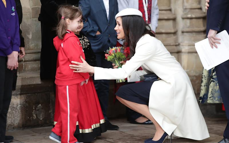 Meghan Markle talking to children as she leaves the Commonwealth Service at Westminster Abbey - PA