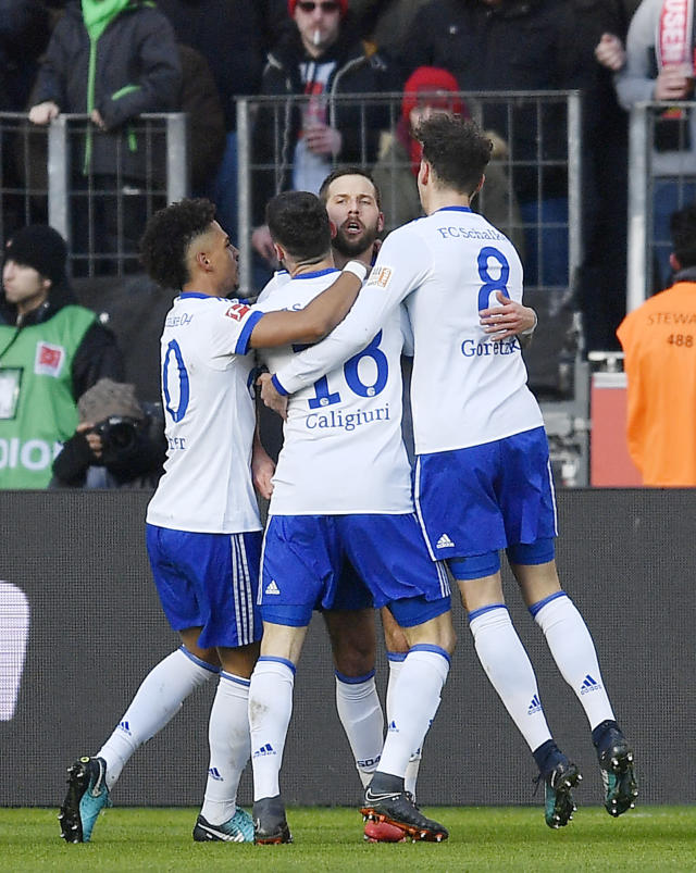 Schalke's Guido Burgstaller, right, celebrates after scoring the opening goal against Leverkusen goalkeeper Bernd Leno during the German Bundesliga soccer match between Bayer Leverkusen and FC Schalke 04 in Leverkusen, Germany, Sunday, Feb 25, 2018. (AP Photo/Martin Meissner)
