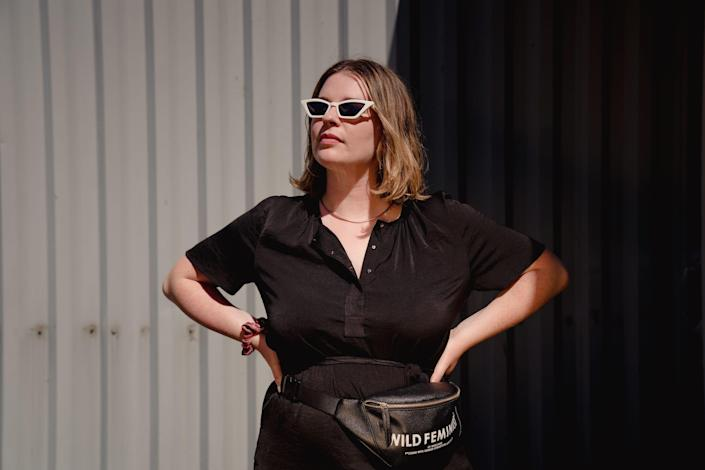 """Tori Dunlap wearing a black short-sleeve dress with a necklace, a pair of white sunglasses, and a fanny pack that says """"Wild Feminist."""""""