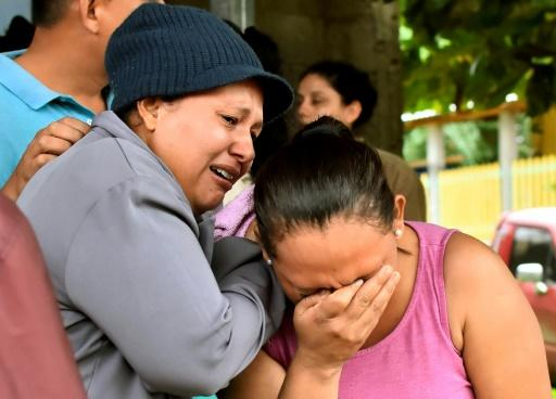 Relatives of inmates react after learning of their loved ones' fate in front of the prison in Tela, Honduras, where overnight rioting claimed at least 18 lives