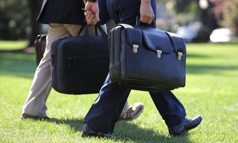 A military aide carries the 'football' across the South Lawn for Barack Obama.