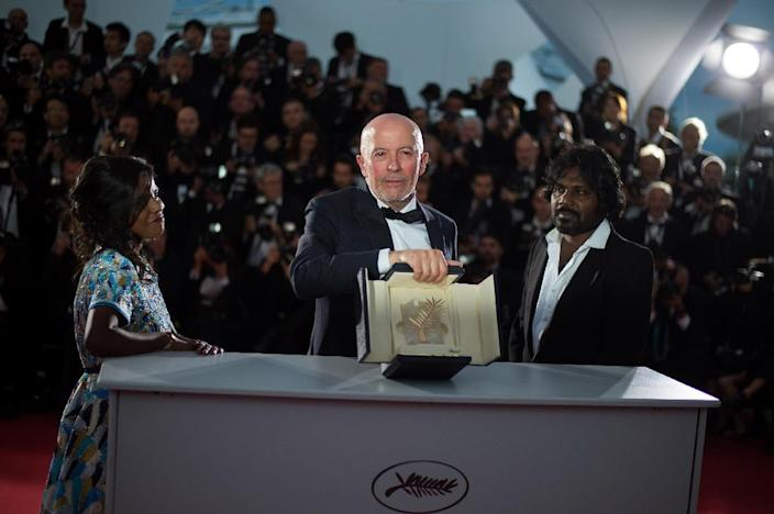 "French director Jacques Audiard (C) stands with Sri Lankan actress Kalieaswari Srinivasan (L) and Sri Lankan actor Jesuthasan Antonythasan after winning the Palme d'Or for his film ""Dheepan"" at the 68th Cannes Film Festival on May 24, 2015 (AFP Photo/Bertrand Langlois)"