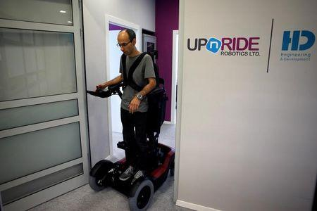 An employee stands on a wheelchair developed by Israeli company UPnRIDE Robotics, that enables paralysed people with limited function in their arms to stand upright, during a demonstration at their offices in Yoqneam, Israel September 6, 2016. REUTERS/Baz Ratner