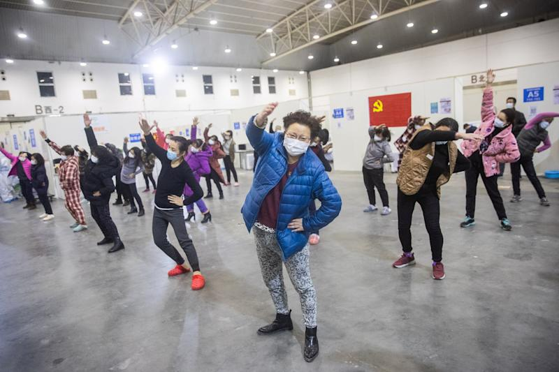 This photo taken on February 17, 2020 shows patients who have displayed mild symptoms of the COVID-19 coronavirus doing exercises at an exhibition centre converted into a hospital in Wuhan in China's central Hubei province. - The death toll from the COVID-19 coronavirus epidemic jumped to 1,868 in China on February 18 after 98 more people died, according to the National Health Commission. (Photo by STR / AFP) / China OUT (Photo by STR/AFP via Getty Images)