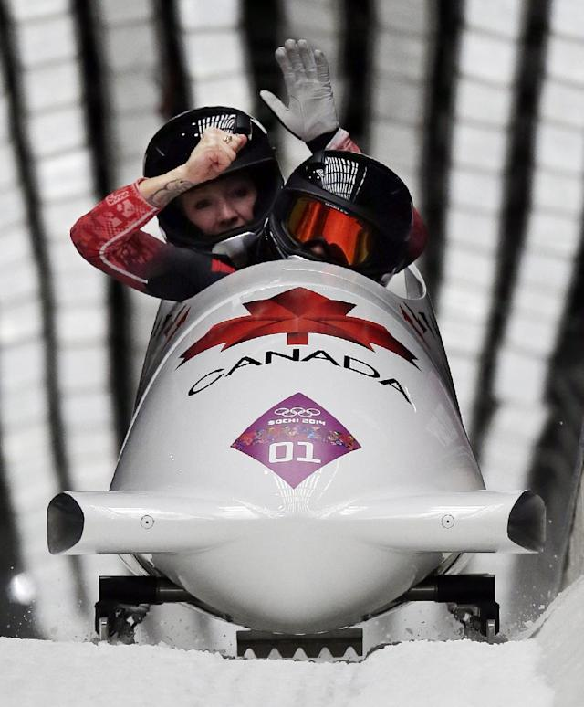 The team from Canada CAN-1, piloted Kaillie Humphries with brakeman Heather Moyse, cross into the finish area to win the gold medal in the women's bobsled competition at the 2014 Winter Olympics, Wednesday, Feb. 19, 2014, in Krasnaya Polyana, Russia. (AP Photo/Michael Sohn)