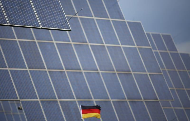 A German national flag is pictured in front of solar panels in Bad Hersfeld