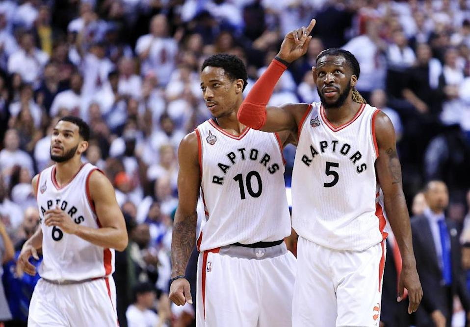 DeMar DeRozan (L) of the Toronto Raptors congratulates DeMarre Carroll after he scored a basket in overtime of game two of the Eastern Conference semi-finals during the 2016 NBA Playoffs at the Air Canada Centre on May 5, 2016 in Toronto, Ontario. Vaughn Ridley/Getty Images/AFP (AFP Photo/Vaughn Ridley)